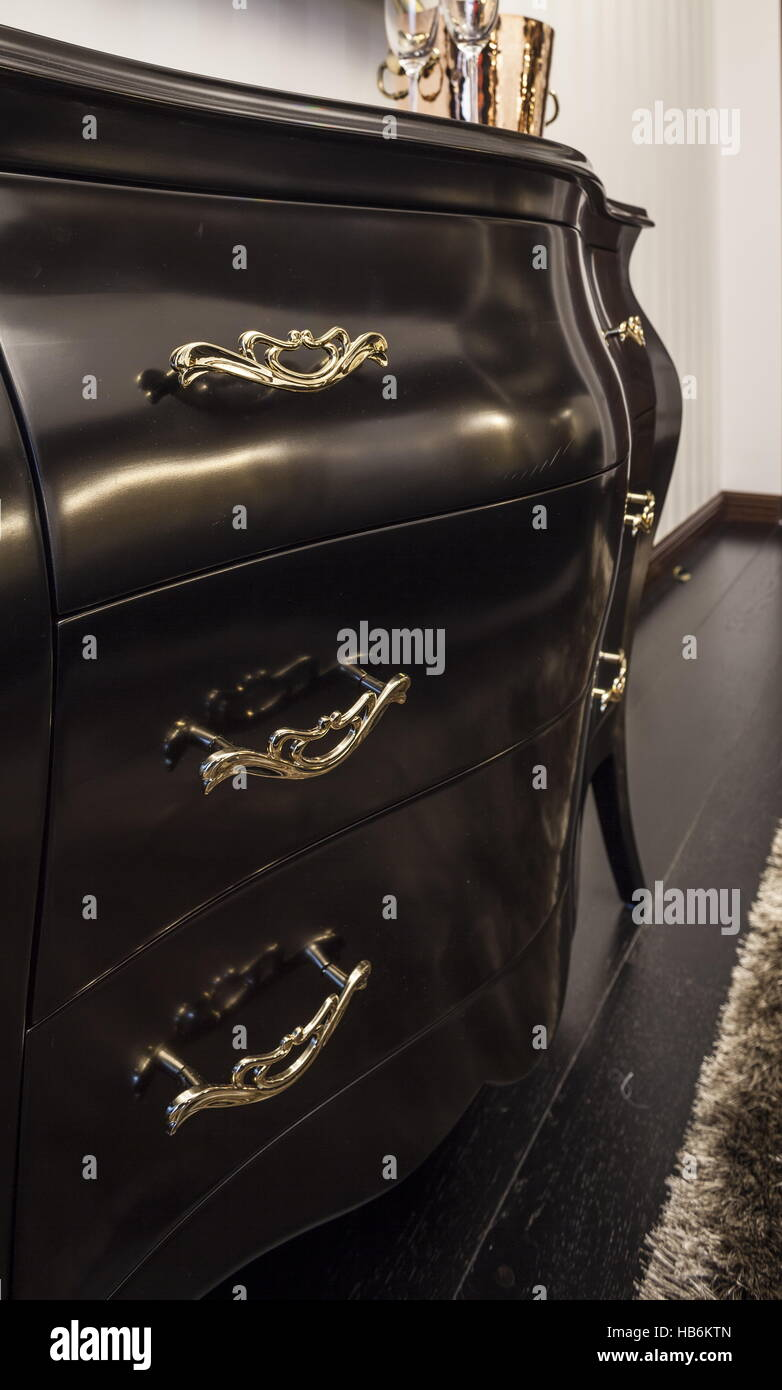 Chest of drawers ebony in interior - Stock Image