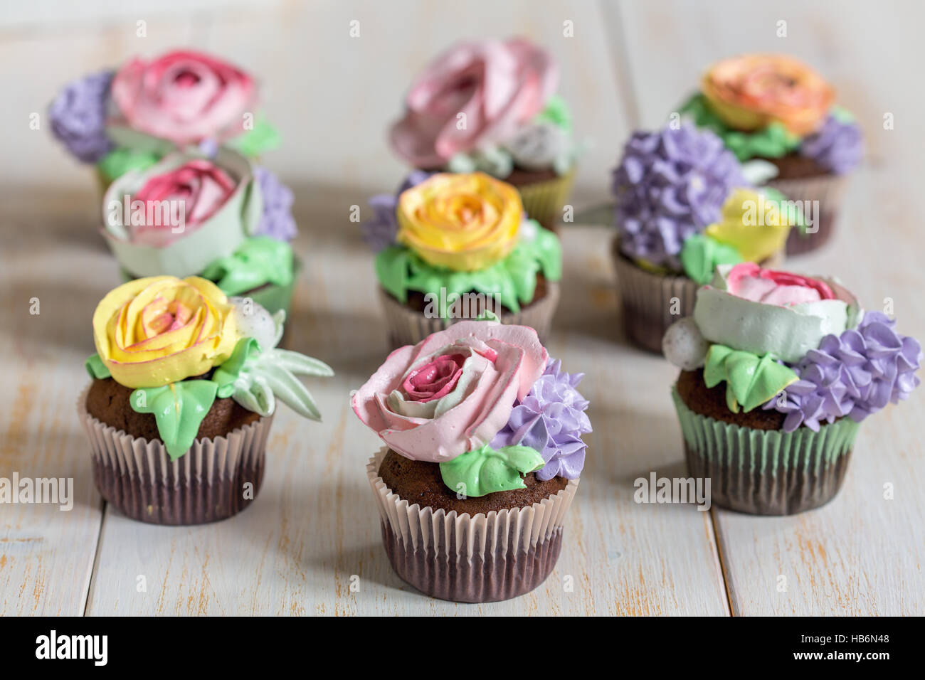 Chocolate cupcakes with cream-colored flowers. - Stock Image