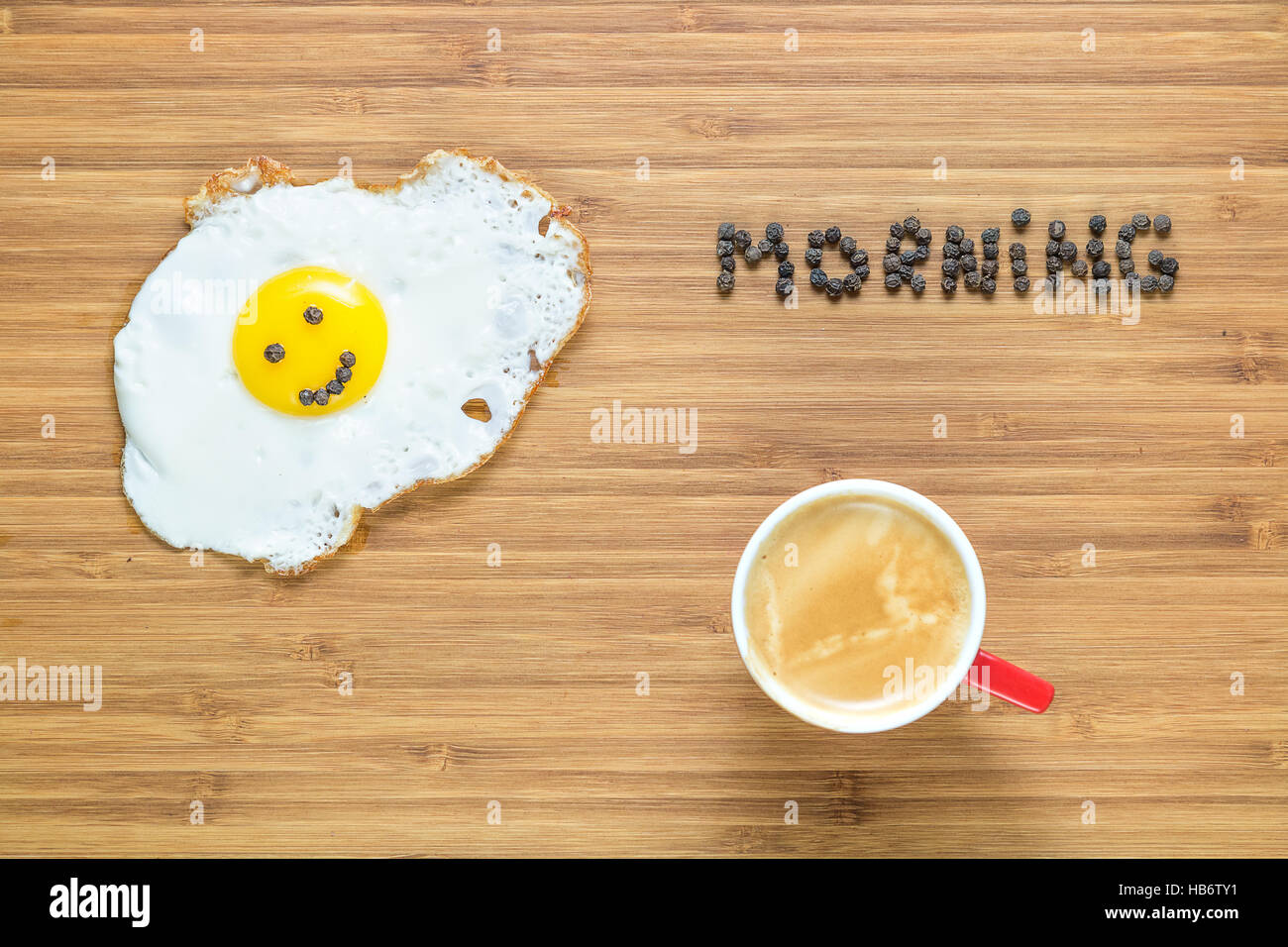 Smiling fried egg lying on a white plate and wooden cutting board with silver fork near it. Classic Breakfast concept. - Stock Image