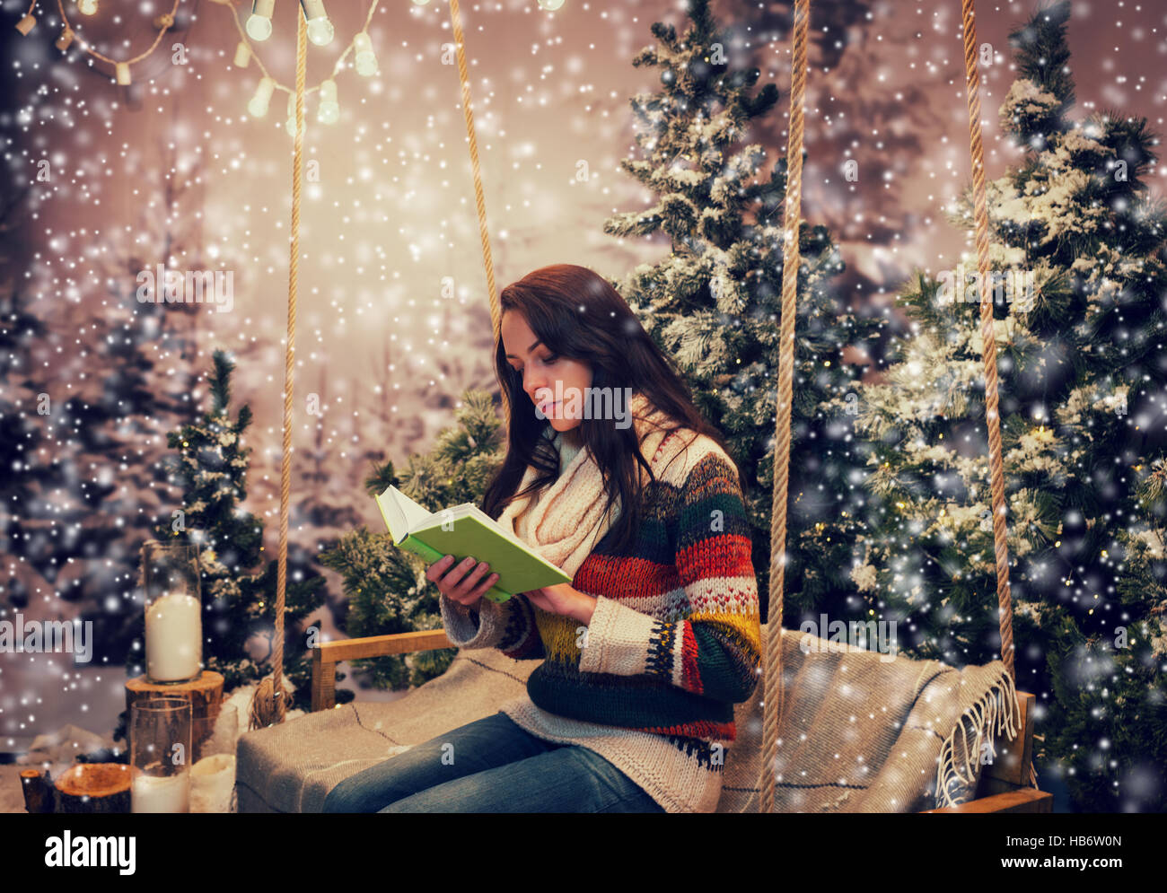 Girl reading under tree stock photos girl reading under tree stock beautiful woman reading a book while sitting on a swing with a blanket under the flashlights sciox Gallery
