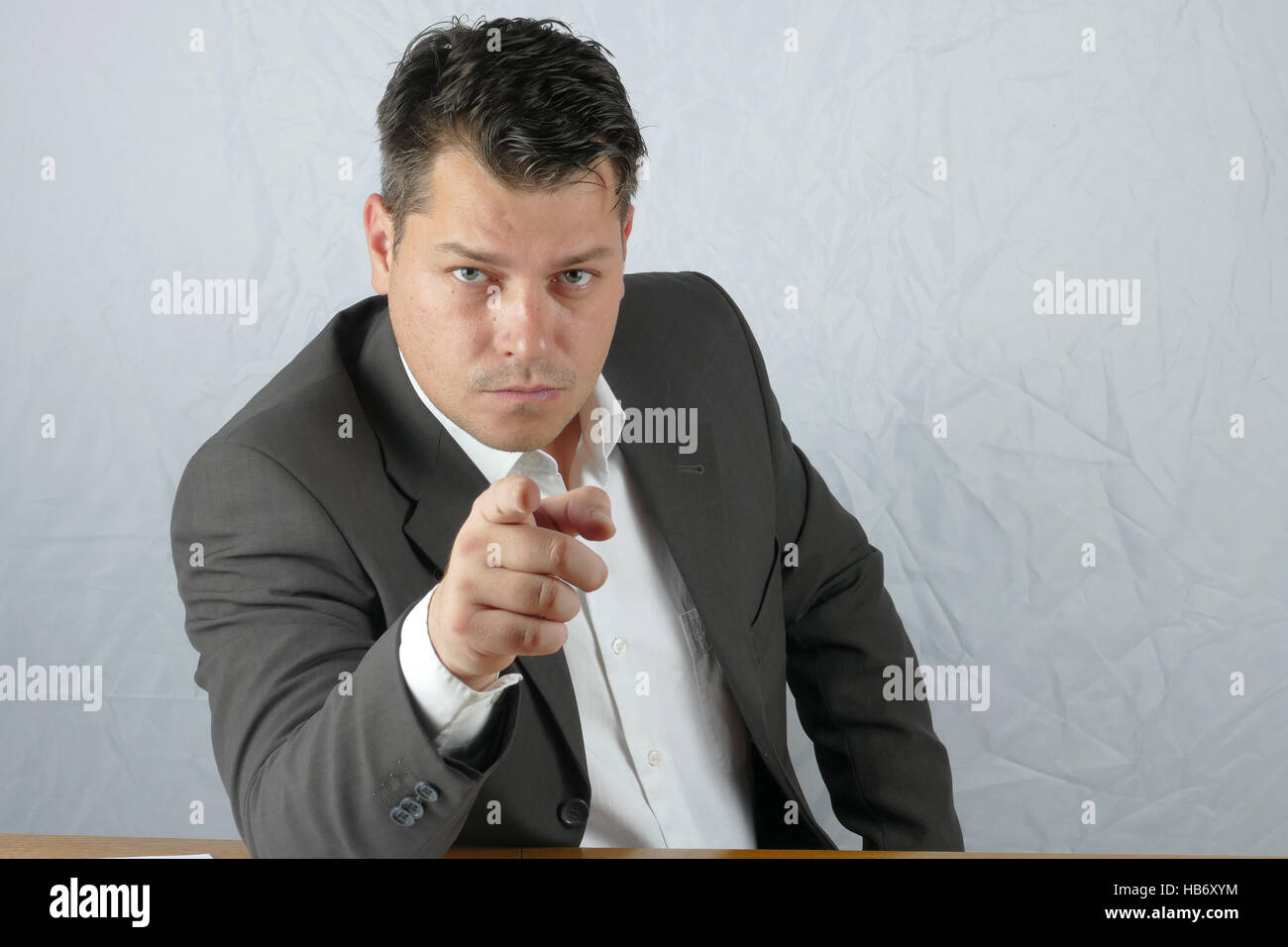 Young angry business man hand mimicry - Stock Image