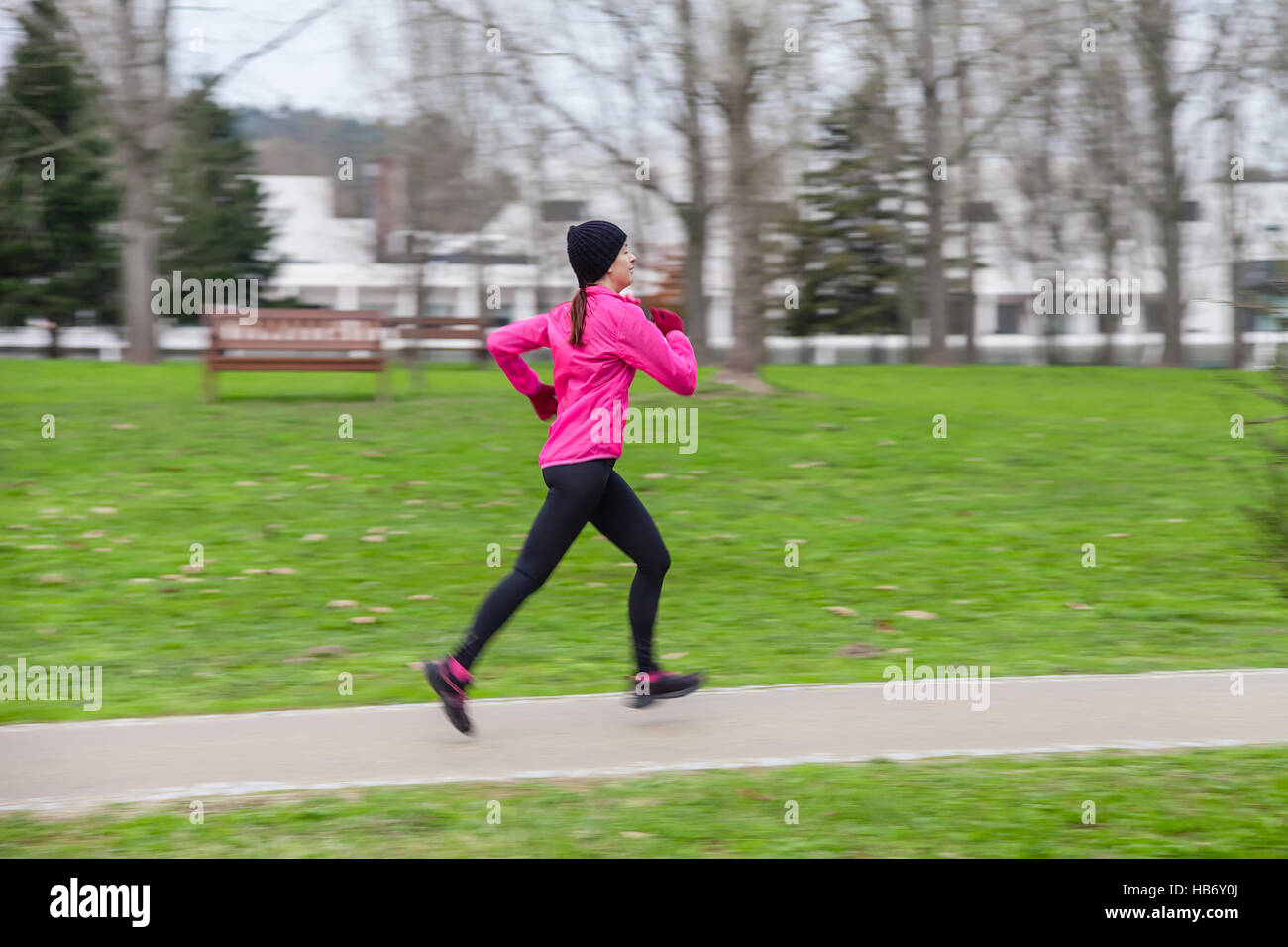 Panning image with motion blur of a young woman running on a cold winter day on an urban park. Profile or side view. - Stock Image