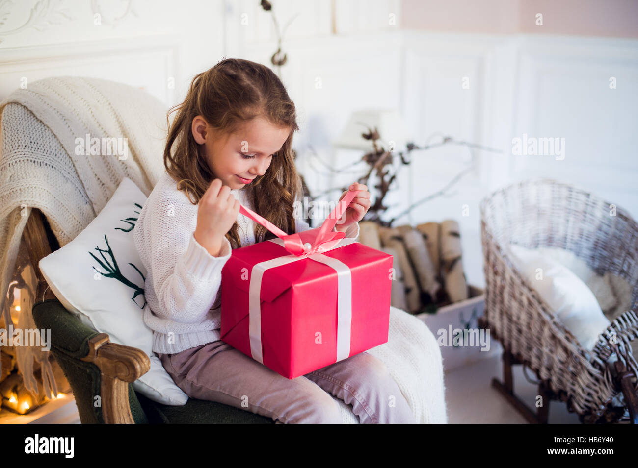 Little girl holding a Christmas gift box. Cute kid sitting on the ...