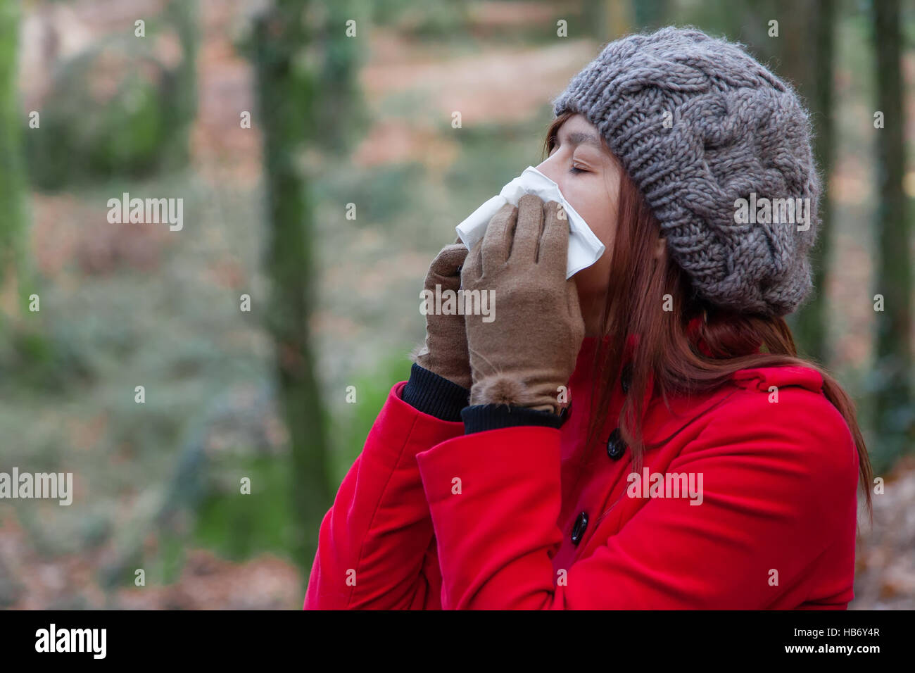 Young woman suffering from a cold, flu or allergies blowing her nose on a white paper handkerchief during winter - Stock Image