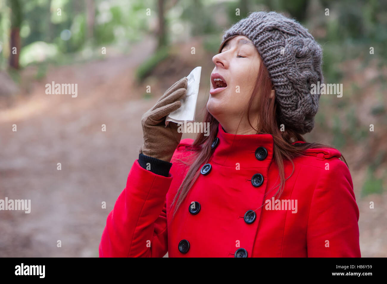 Young woman suffering from a cold, flu or allergies sneezing on a paper handkerchief during winter - Stock Image
