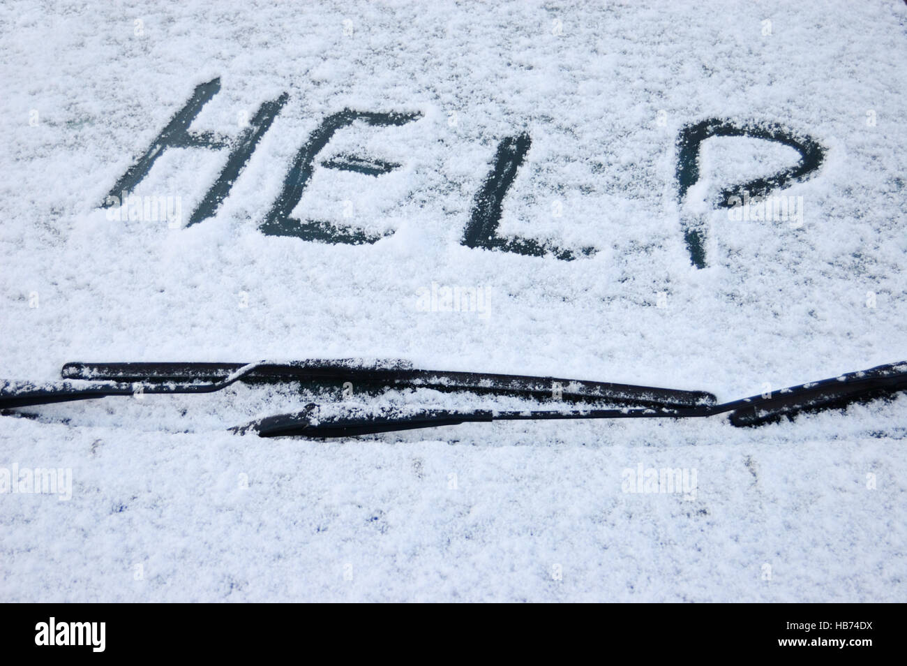 Snow covered car windscreen with the word help written in the snow Stock Photo