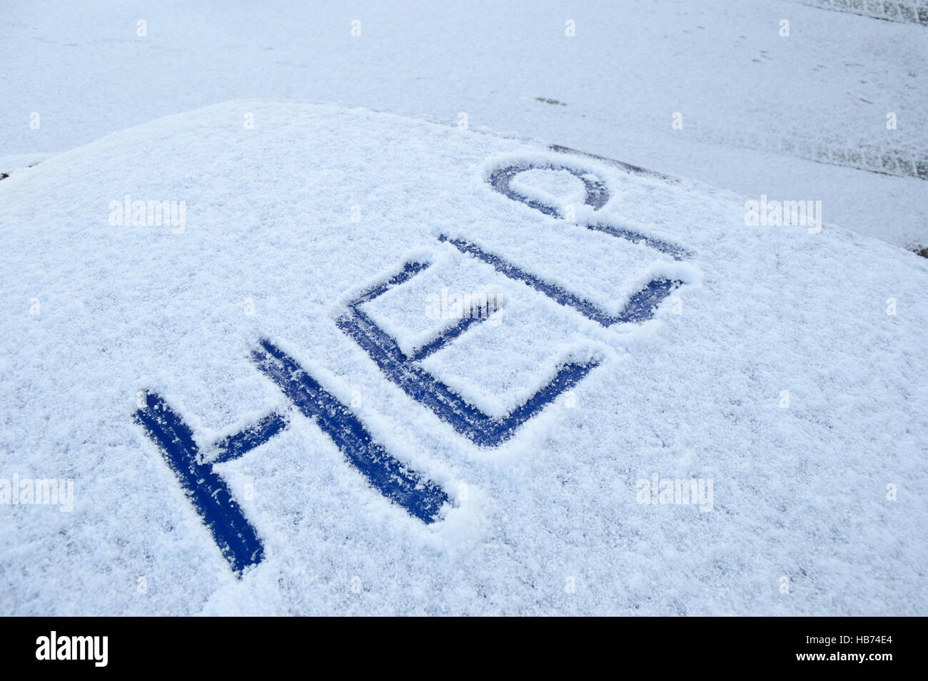 Snow covered car roof with the word help written in the snow Stock Photo