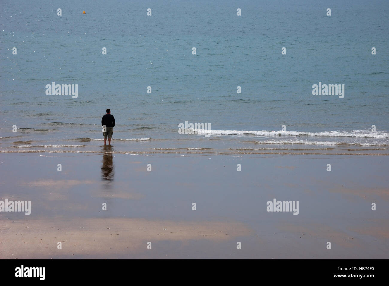 Solitary man wearing shorts standing on the edge of a beach looking out to sea Stock Photo