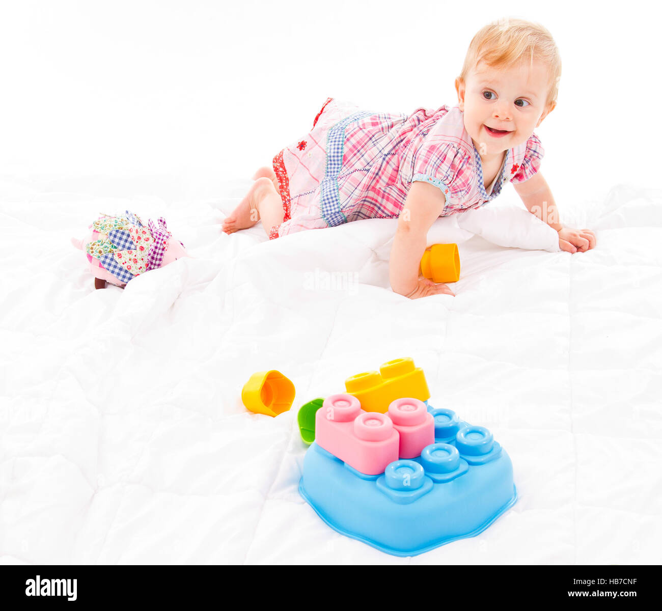 cute baby girl wearing a dress is crawling  on a white blanket  with some building blocks on it - Stock Image