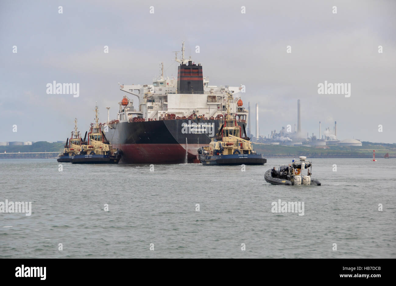 Super tanker Stavanger Prince being assisted into Milford Haven by three tugs under the watchful gaze of the police - Stock Image