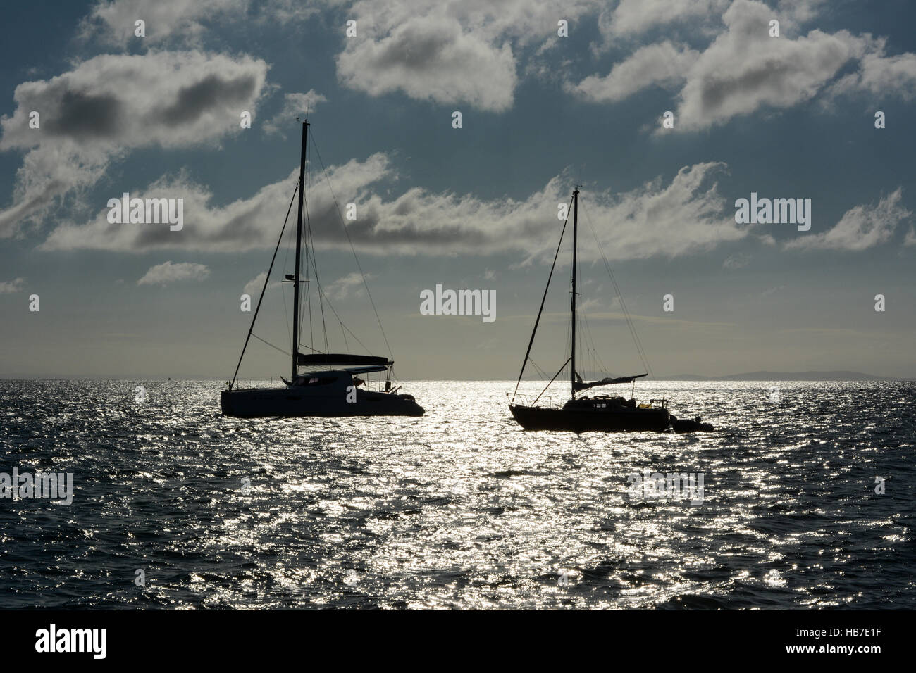 Two yachts anchored in Tenby bay early on a summer morning. Blue sky with white fluffy clouds and the sun reflecting - Stock Image