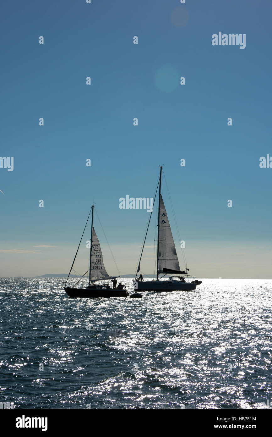 Two yachts anchored in Tenby bay prepare to set sail on a blue cloudless sky and the sun reflecting on the sea. - Stock Image
