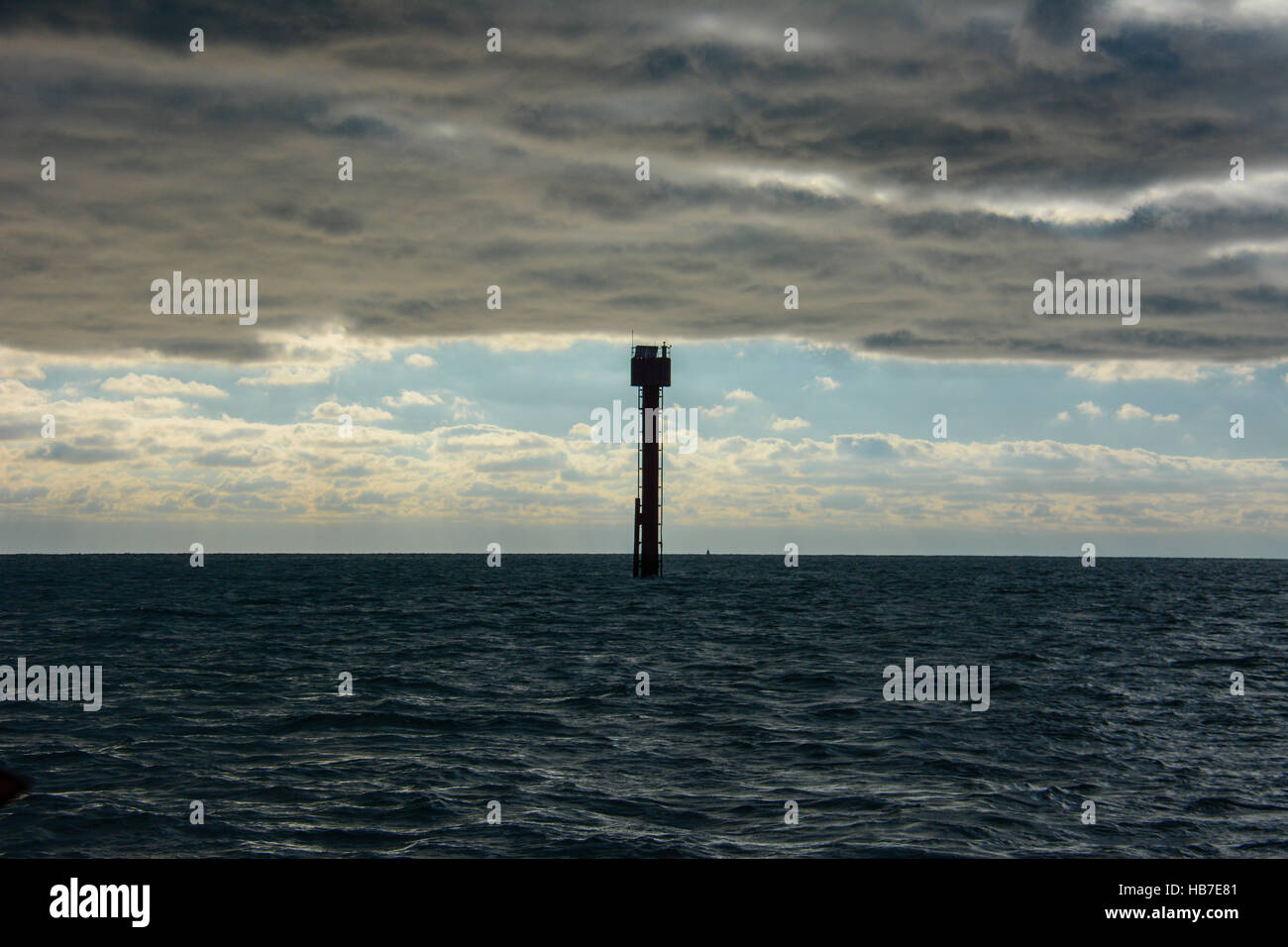 Mid channel marker post seems to be holding up the strong November sky full of clouds over the dark blue sea Stock Photo