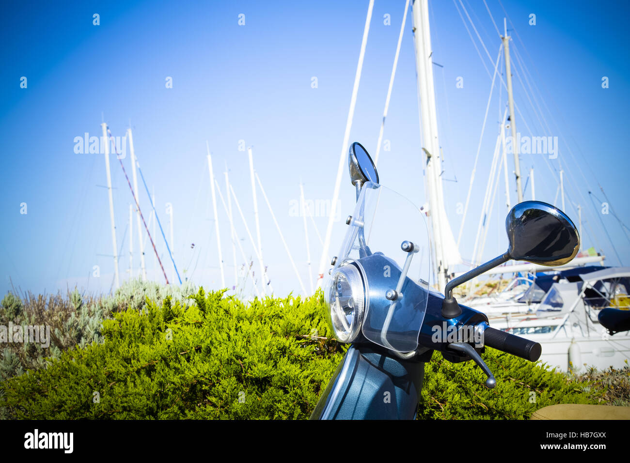 vintage scooter in the harbour with spars in background - Stock Image