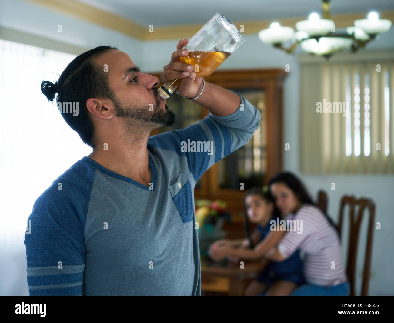 Social issues, abuse and aggression on women, alcoholic latino man and sad woman crying at home. Violent husband - Stock Image