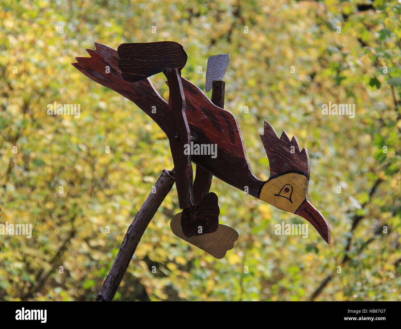 Wooden roadrunner whirligig with autumn trees in background - Stock Image