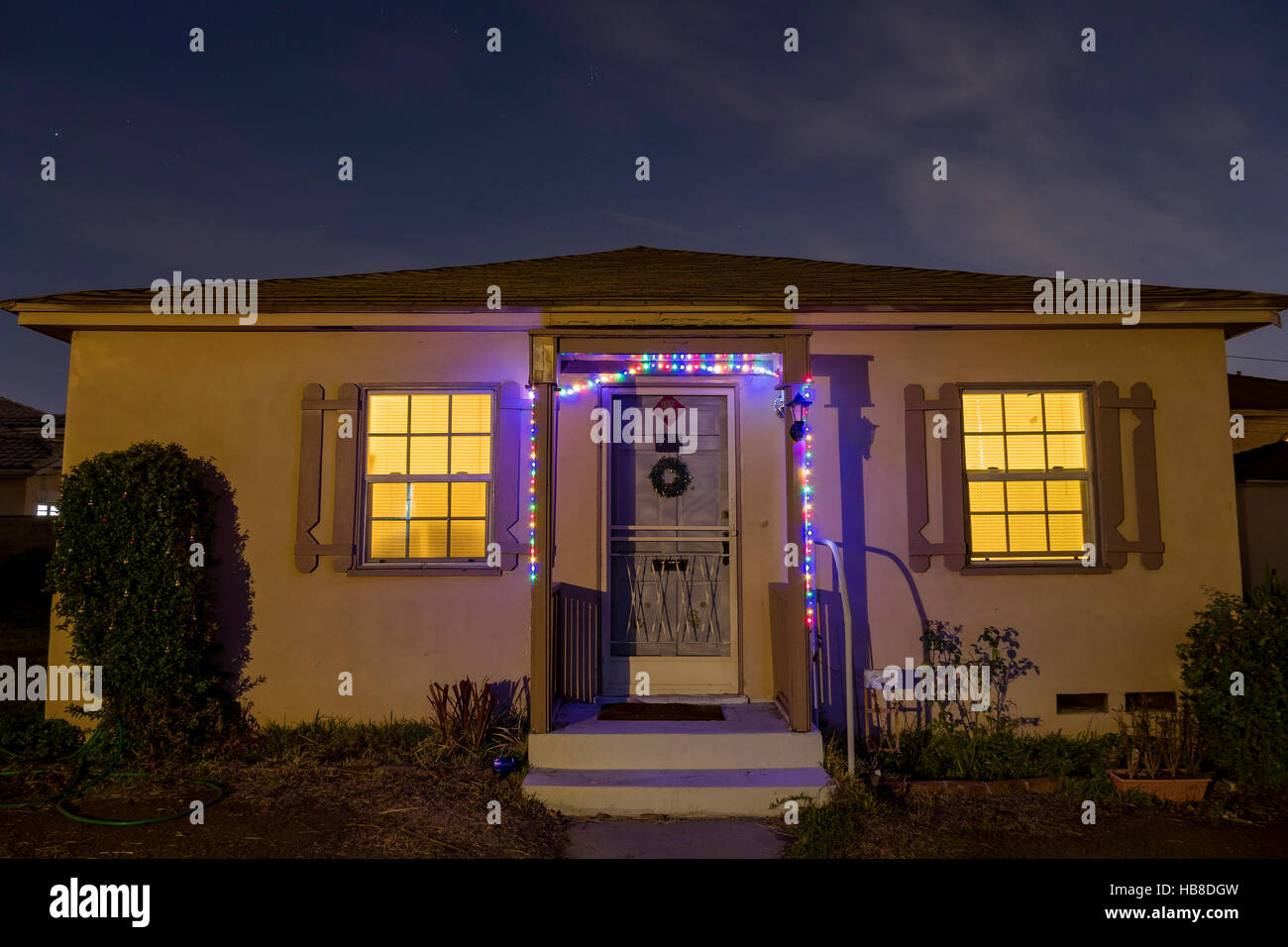Simple Christmas Decoration Of A Wooden Typical Small American House At Night With Lights