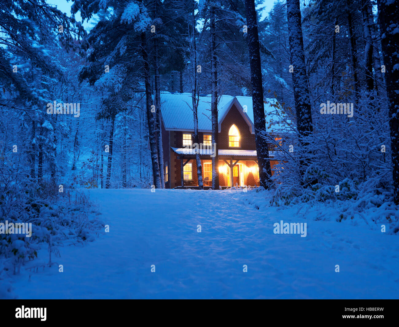 Brick country house or cottage with lights, snowy winter evening twilight, Muskoka, Ontario, Canada - Stock Image