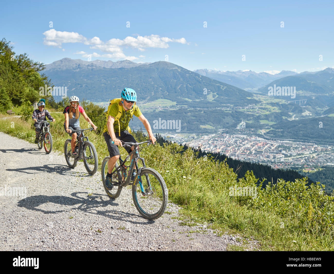 Family on mountain bikes, dirt road, Innsbruck behind, Inn Valley, Tyrol, Austria - Stock Image