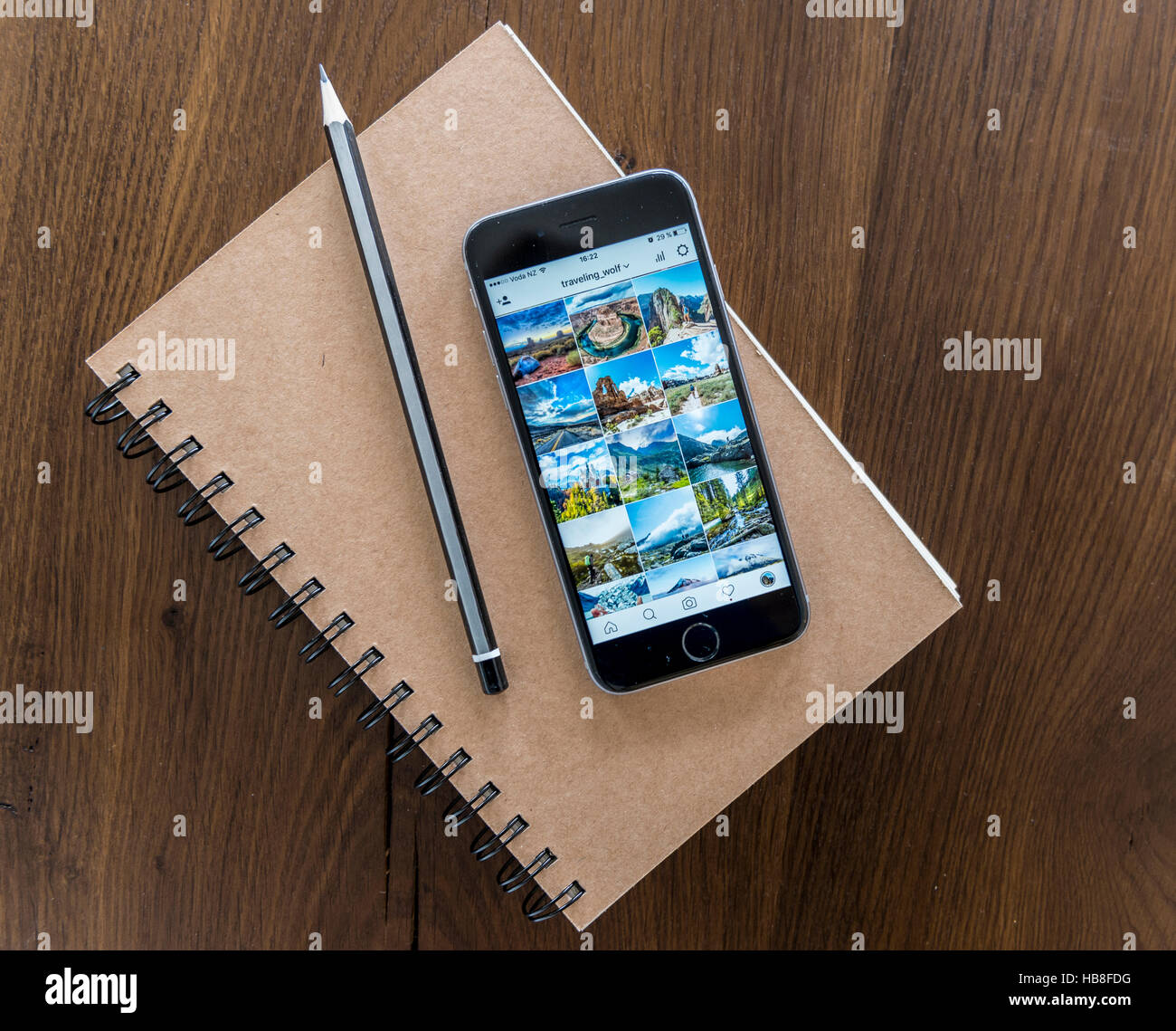 Instagram picture gallery displayed on smartphone screen, notebook and pen on a wooden table - Stock Image