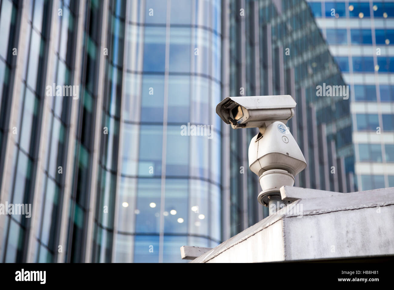 A CCTV surveillance camera with modern skyscrapers in the background Stock Photo