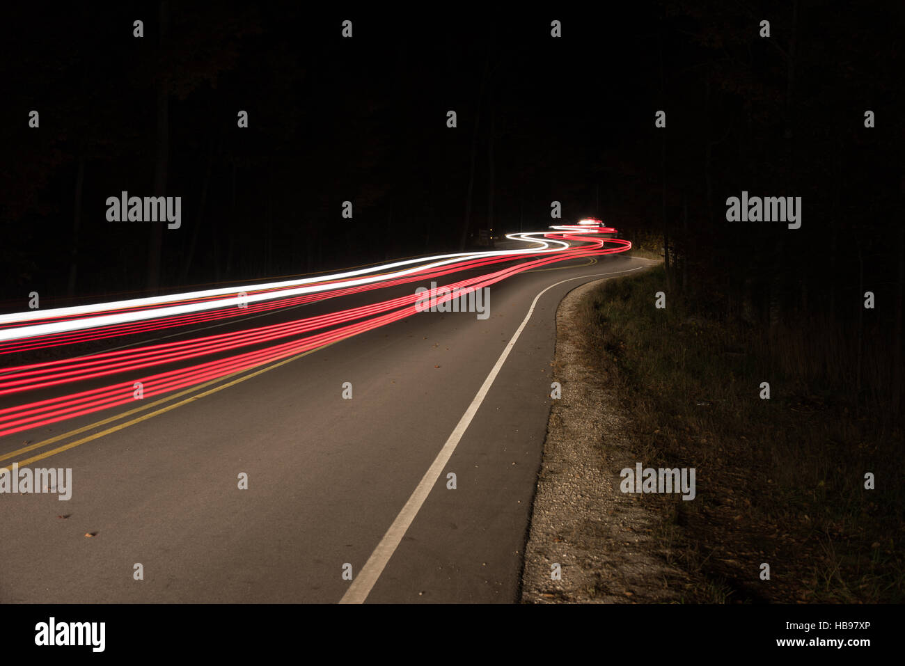 Curved road at night with cars driving up and down causing light trails. - Stock Image