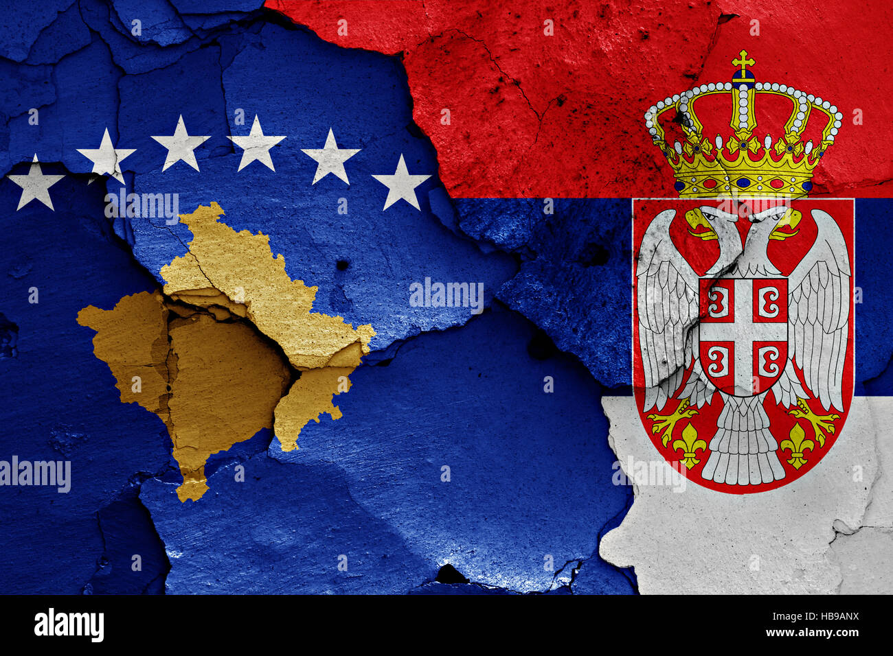 flags of Kosovo and Serbia painted on cracked wall Stock Photo