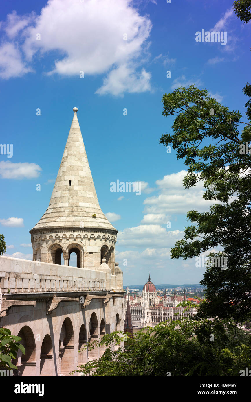 Fisherman's Bastion in the Castle Hill district, across the Danube River from Parliament House (in the distance). - Stock Image