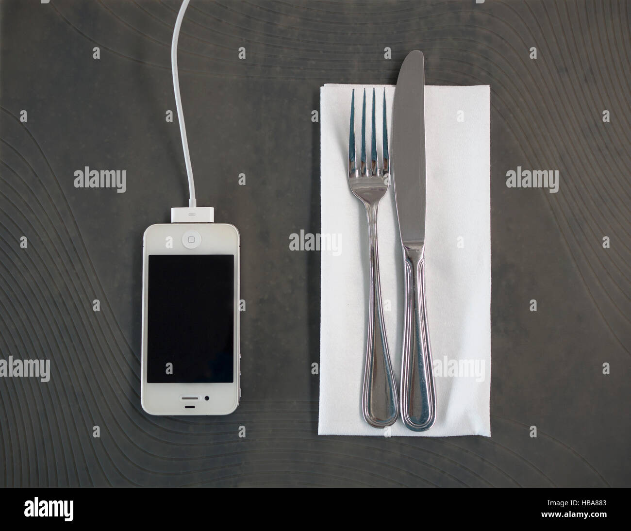 iPhone charging on table with cutlery at airport restaurant - Stock Image
