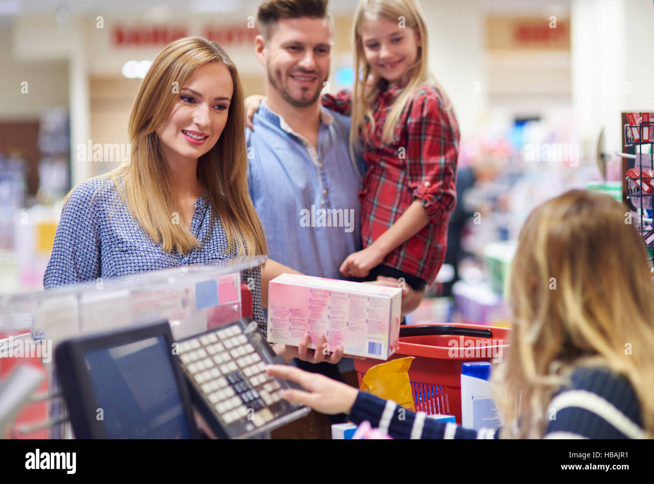 Family packing shopping at supermarket checkout - Stock Image