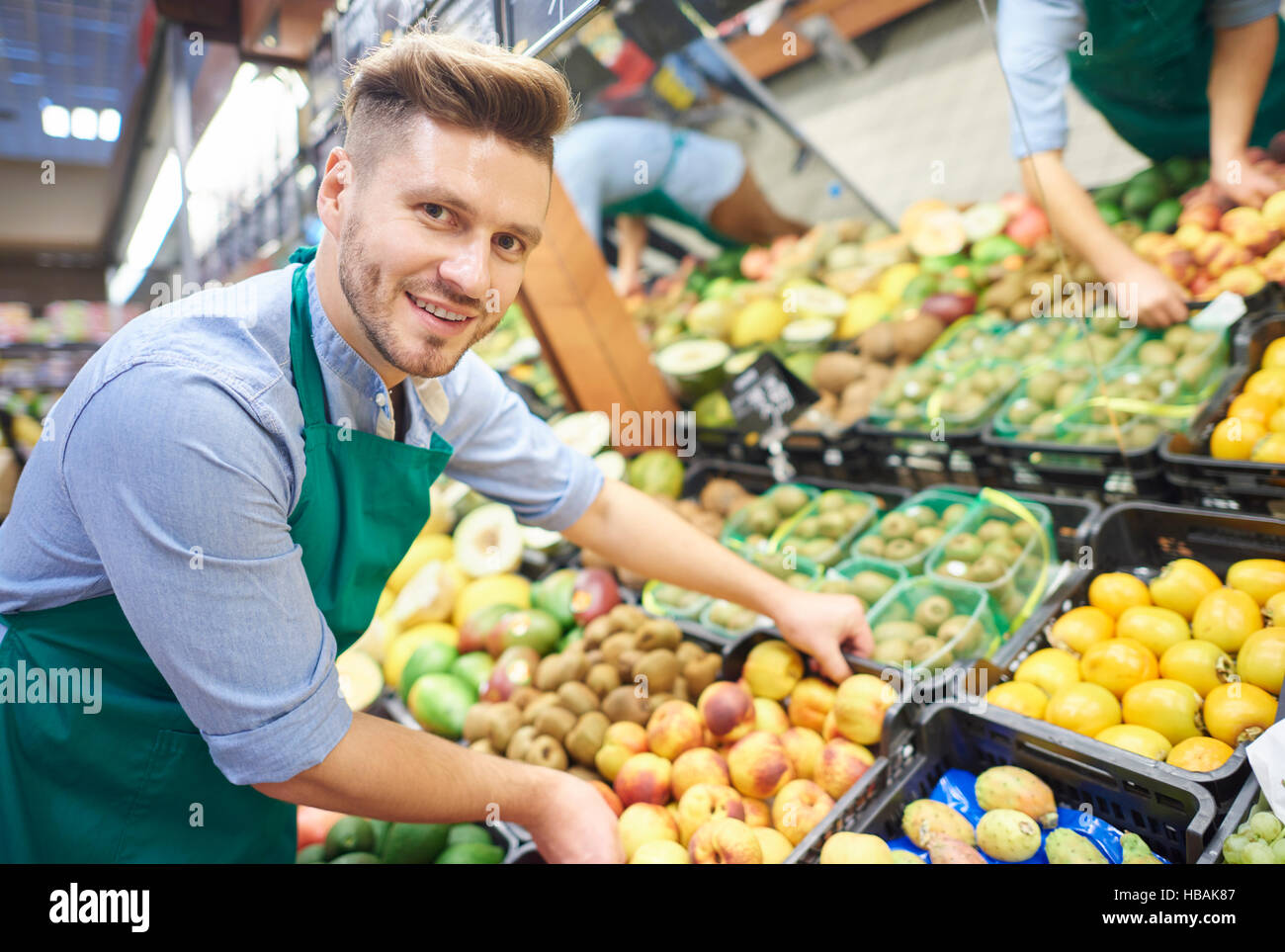 Man working hard in supermarket - Stock Image