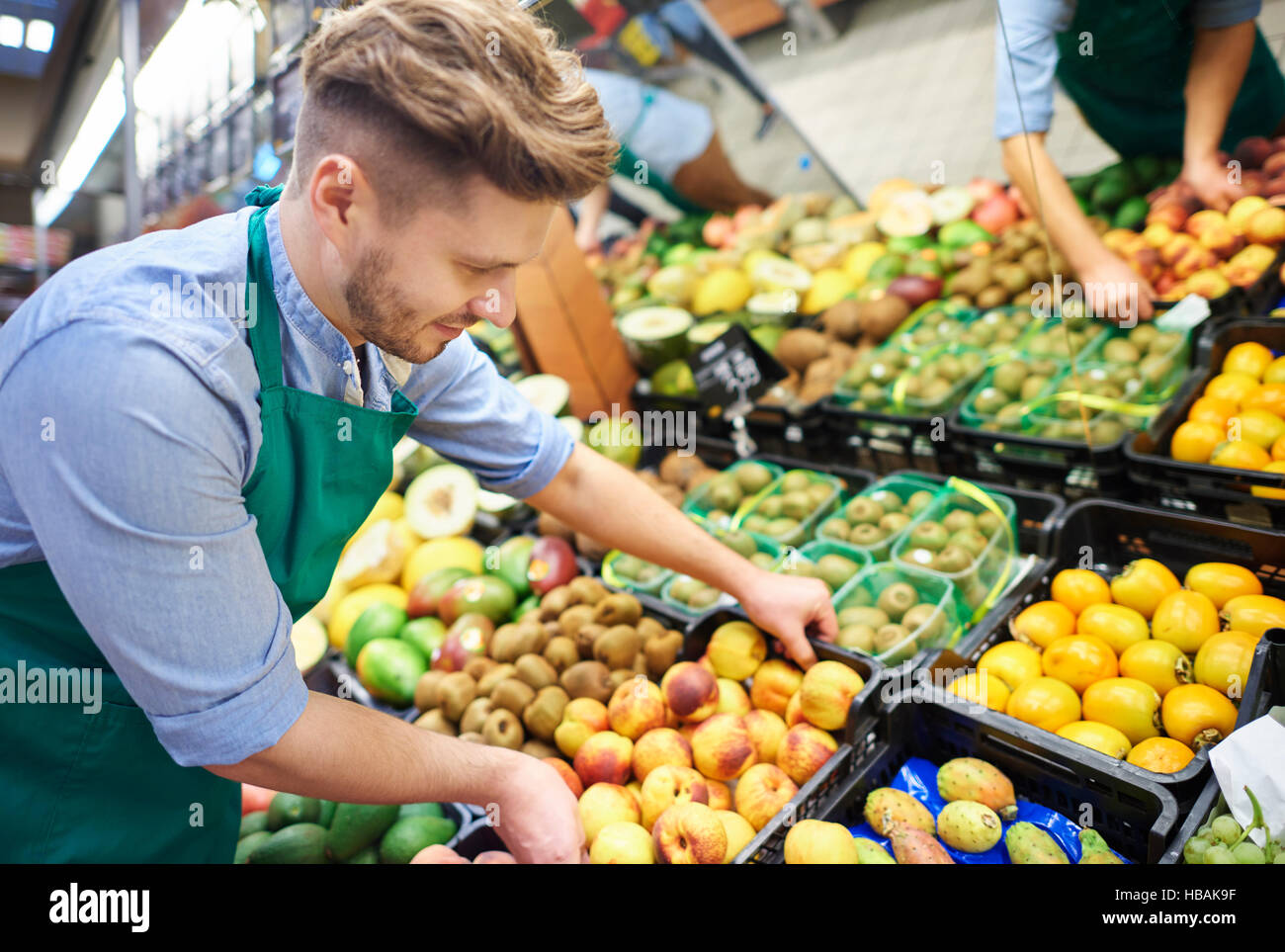 Sales clerk grabbing the box of fruits - Stock Image