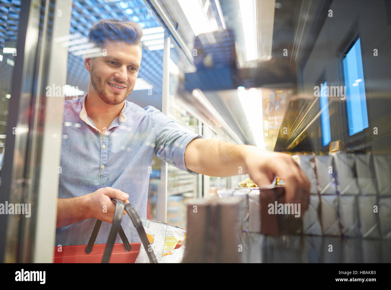 Man shopping for groceries in supermarket freezer - Stock Image