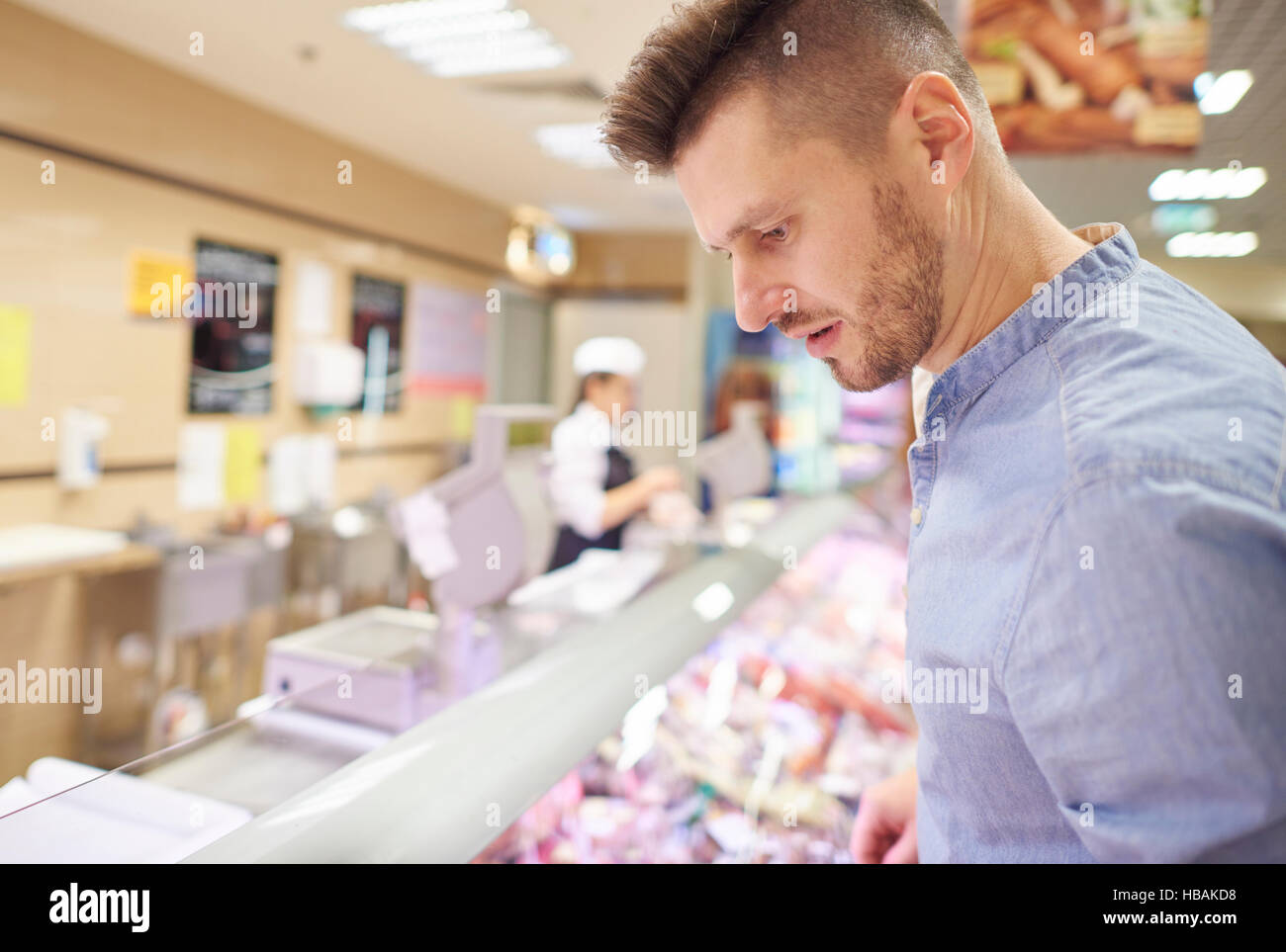 Man looking for products in meat area - Stock Image