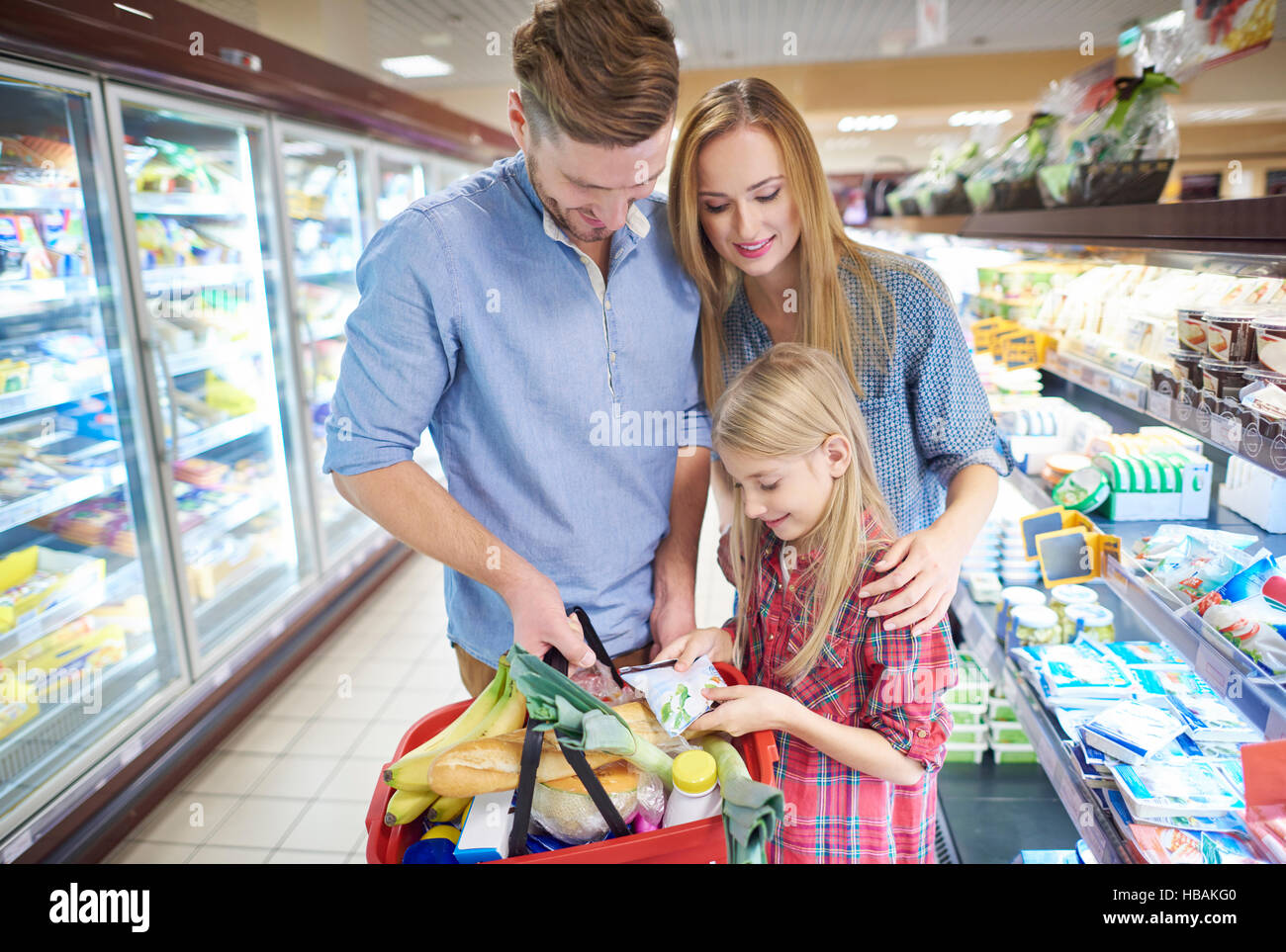 Family in supermarket aisle with full shopping basket - Stock Image