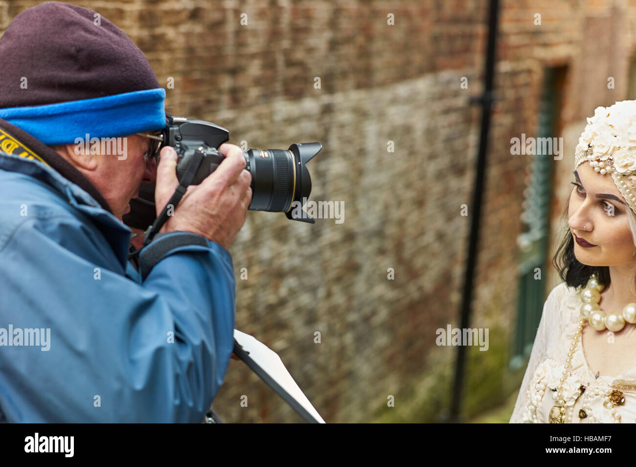 Photographer taking photo of young woman in Whitby goth weekend - Stock Image