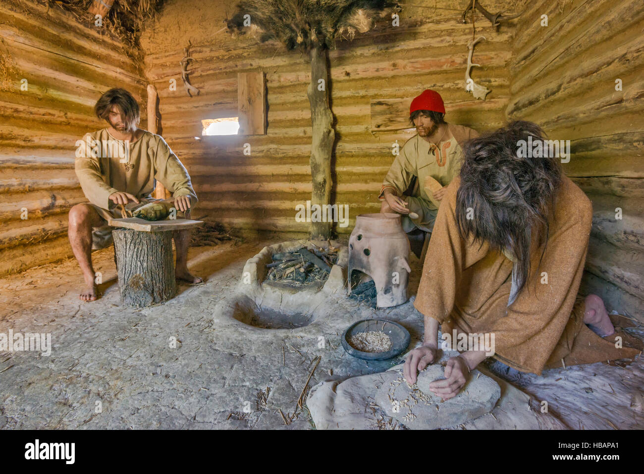 Men preparing food, life-size diorama, Carpathian Troy Archaeological Open-Air Museum in Trzcinica near Jaslo, Malopolska, - Stock Image