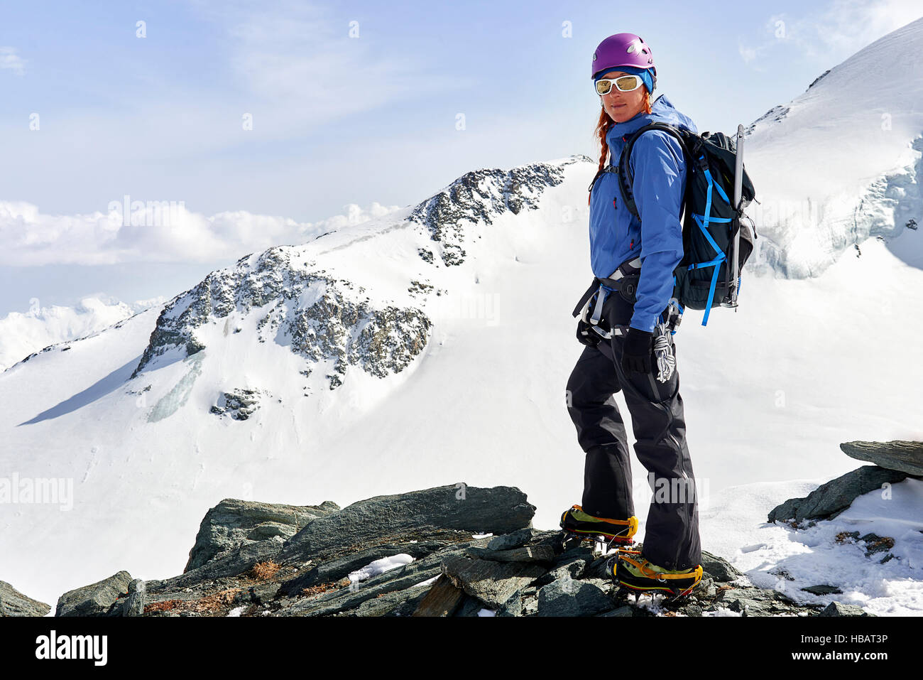 Woman standing in top of snow covered mountain, Saas Fee, Switzerland - Stock Image