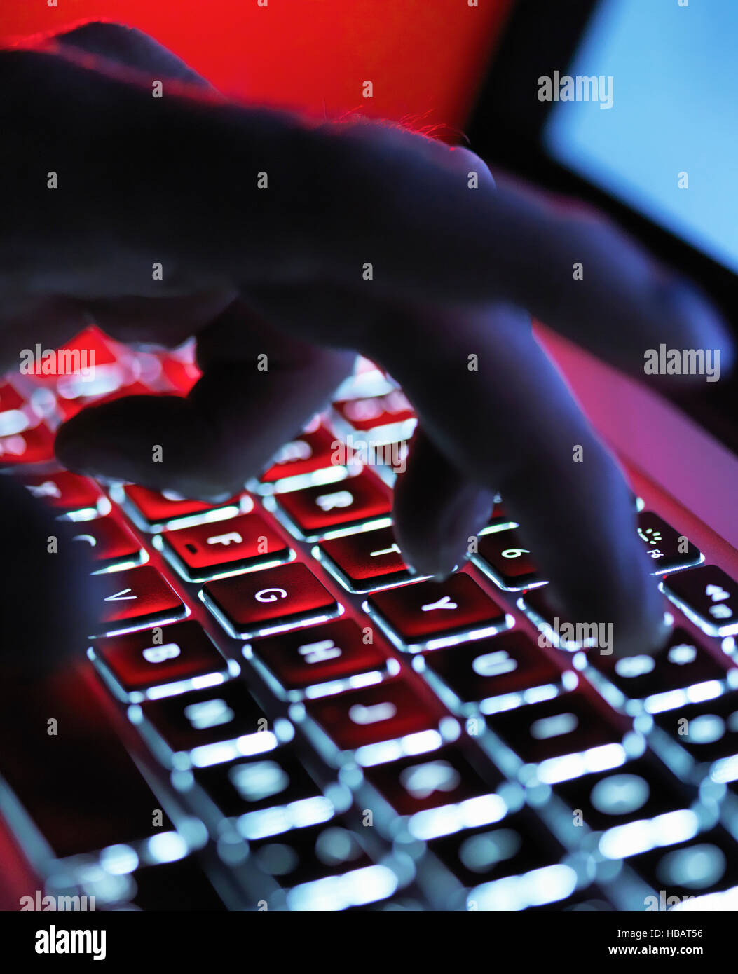A dark mystery hand typing on a laptop computer at night - Stock Image
