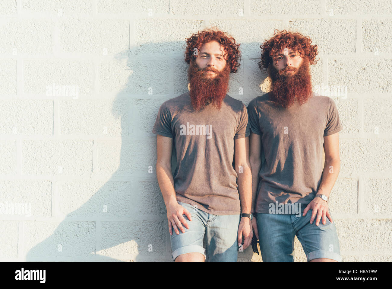 Portrait of identical adult male twins with red hair and beards against wall Stock Photo