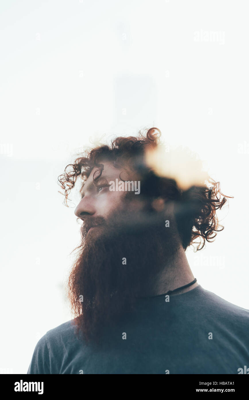 Low angle lens flare portrait of bearded hipster - Stock Image