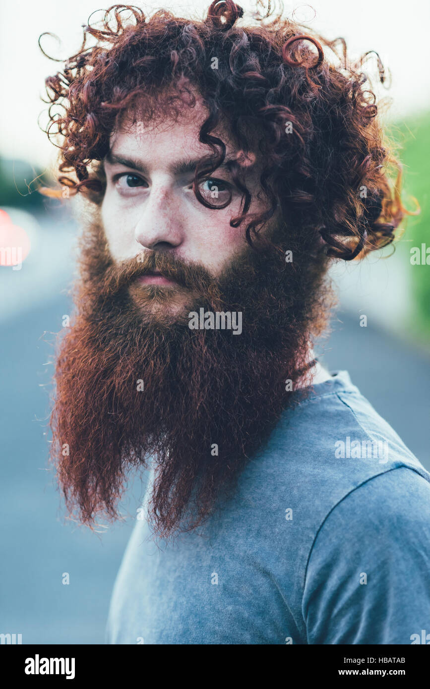 Portrait of curly haired, bearded young male hipster - Stock Image