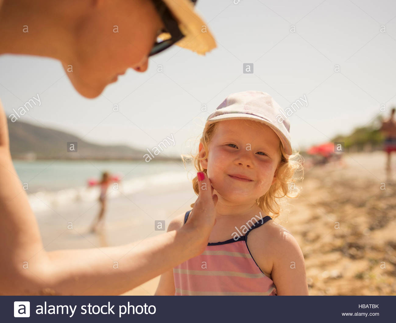 Woman applying suncream to daughter's face on beach, Altea, Alicante Province, Spain - Stock Image
