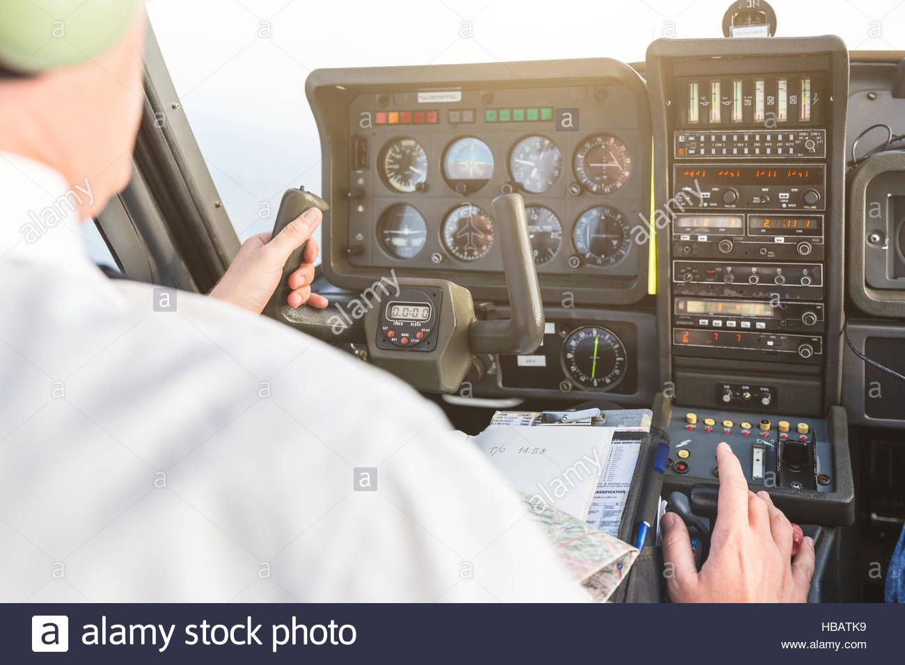 Rear view of pilot in cockpit of aircraft, in flight - Stock Image