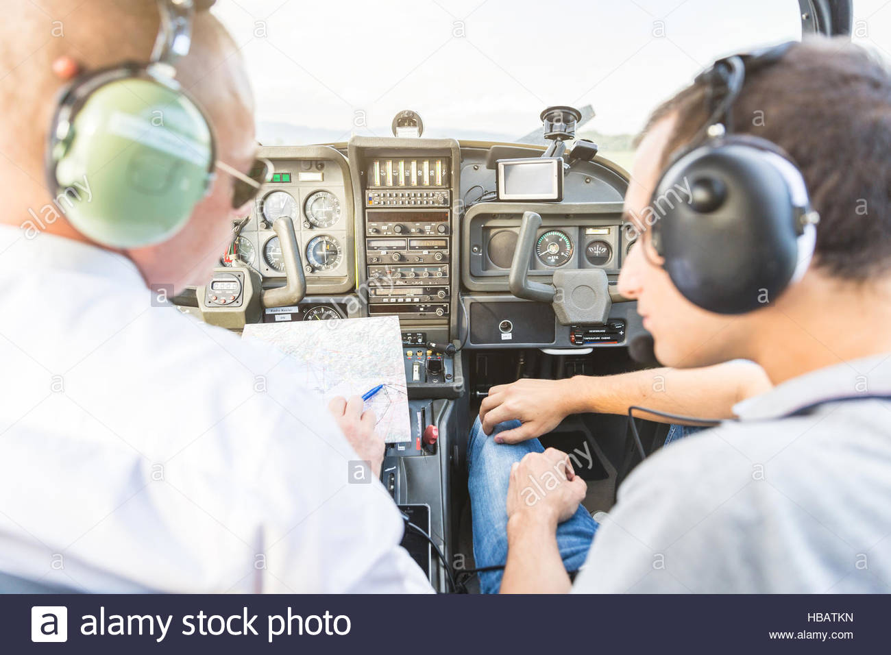 Rear view of pilot and co-pilot sitting in aircraft, talking through flight plan - Stock Image