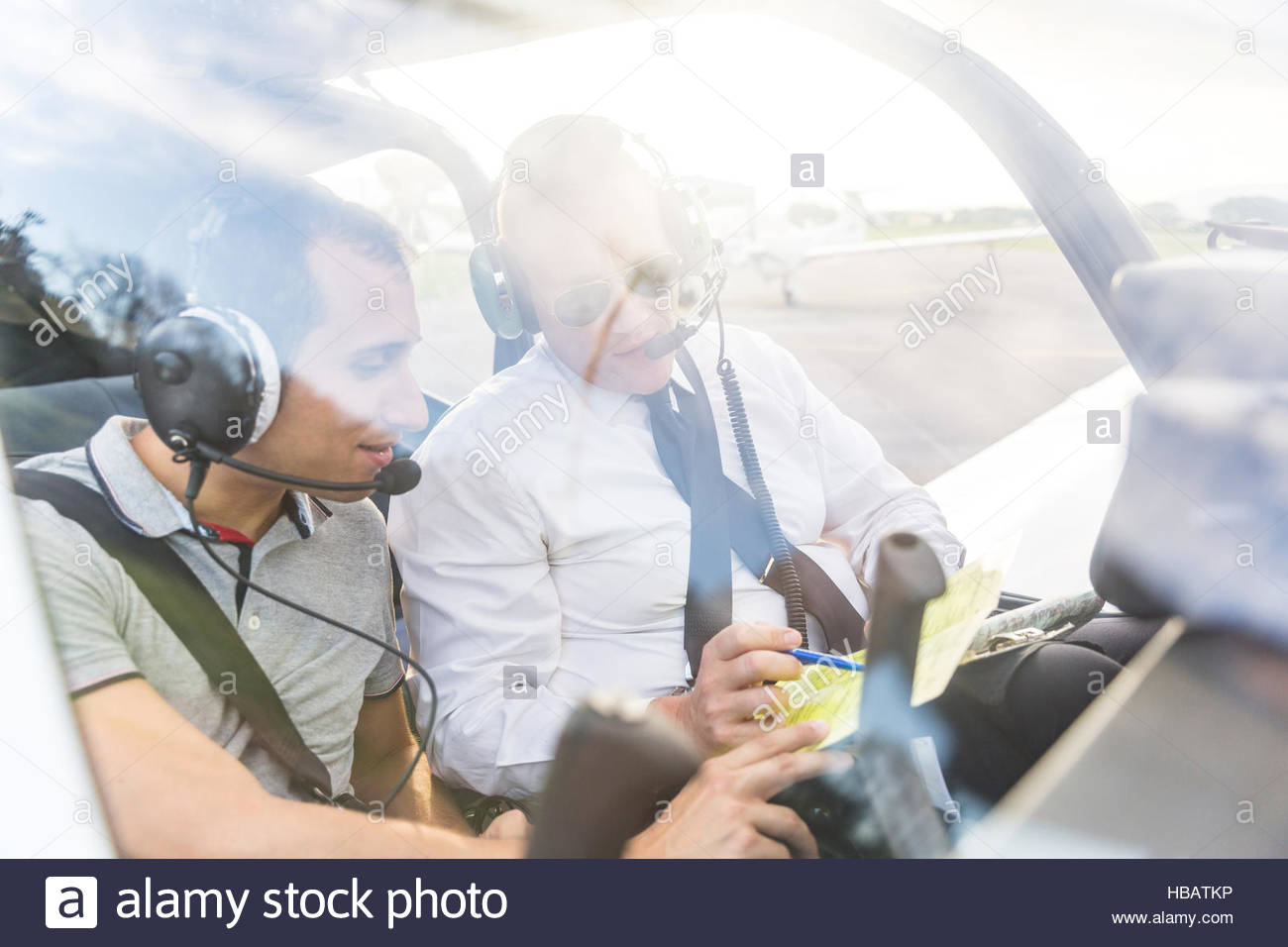 Pilot and co-pilot sitting in aircraft, talking through flight plan - Stock Image