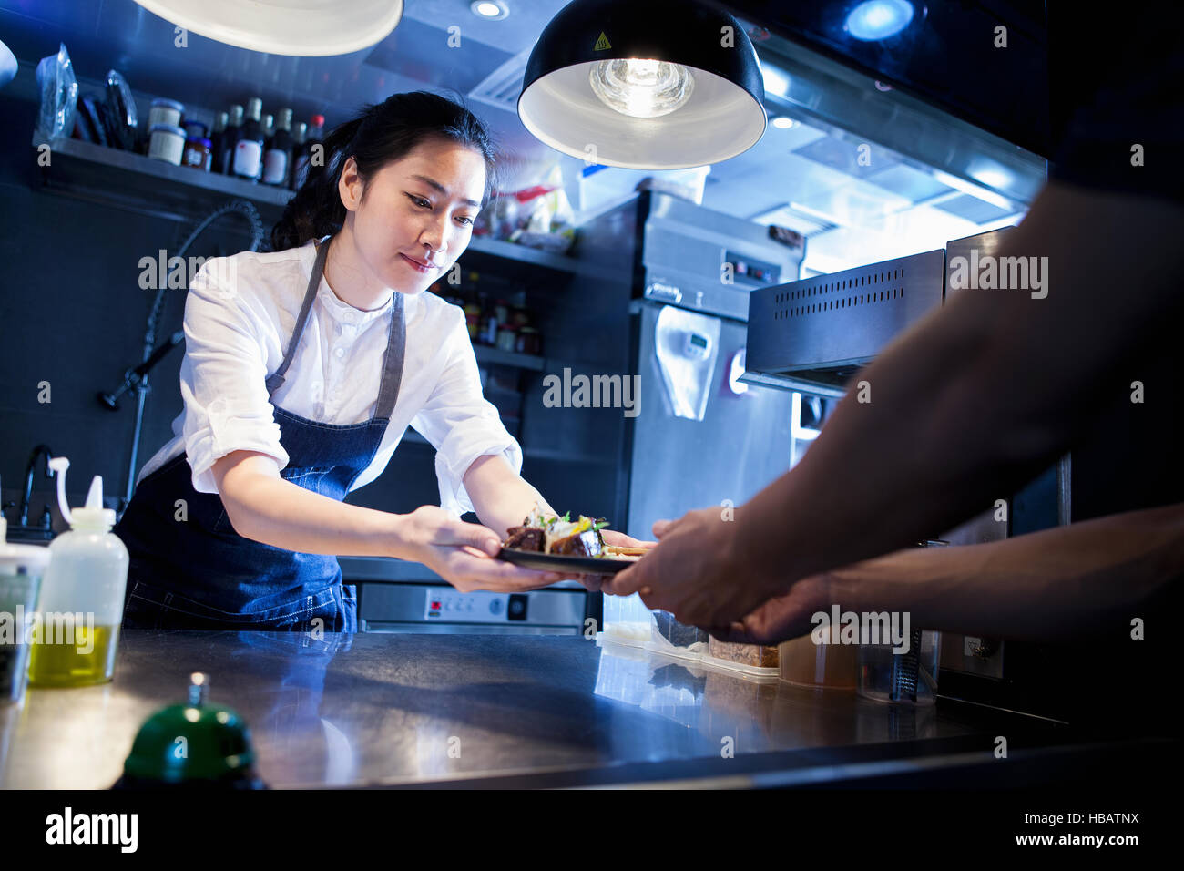 Chef handing prepared meal to waiter - Stock Image