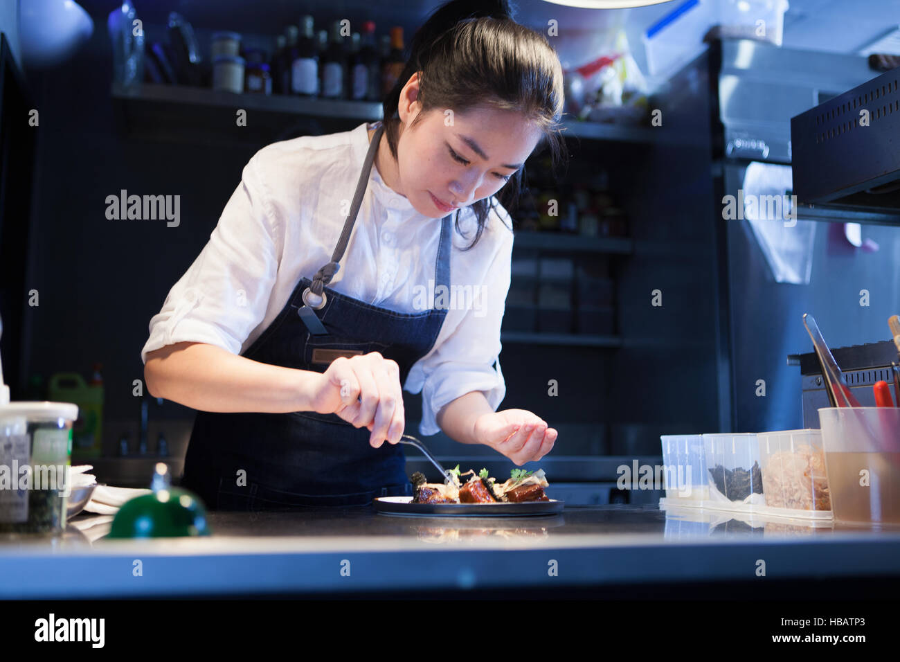 Chef in commercial kitchen seasoning food - Stock Image