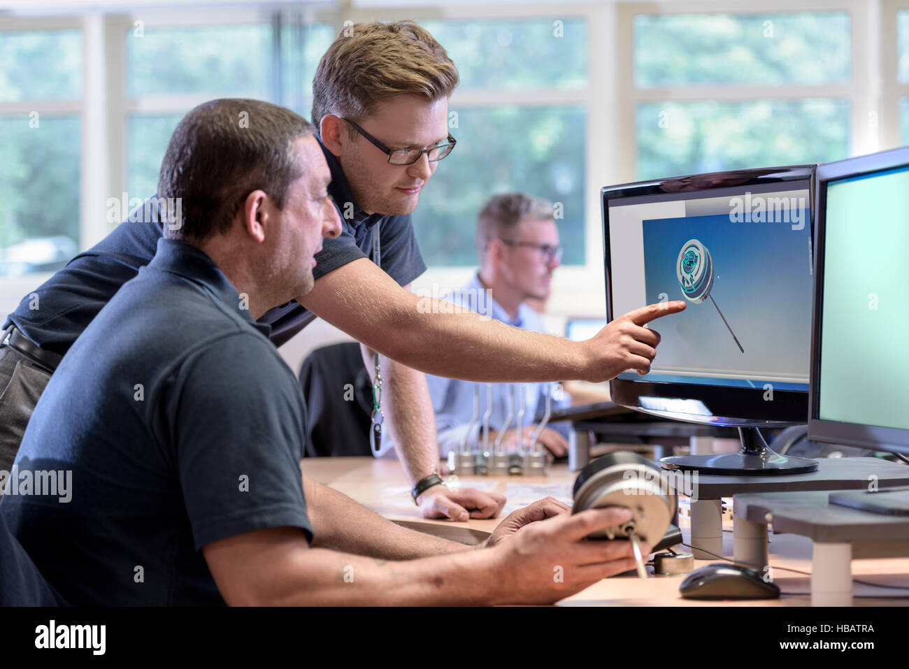 Engineers discussing CAD drawings onscreen of exhaust valve actuator in factory - Stock Image