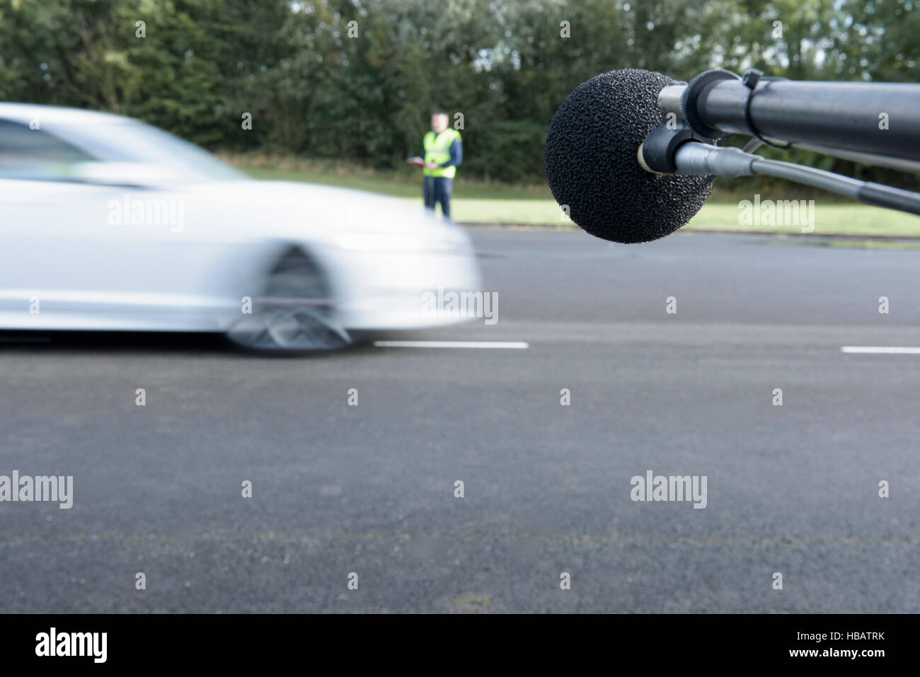 Engineer measuring vehicle sound level at test track - Stock Image